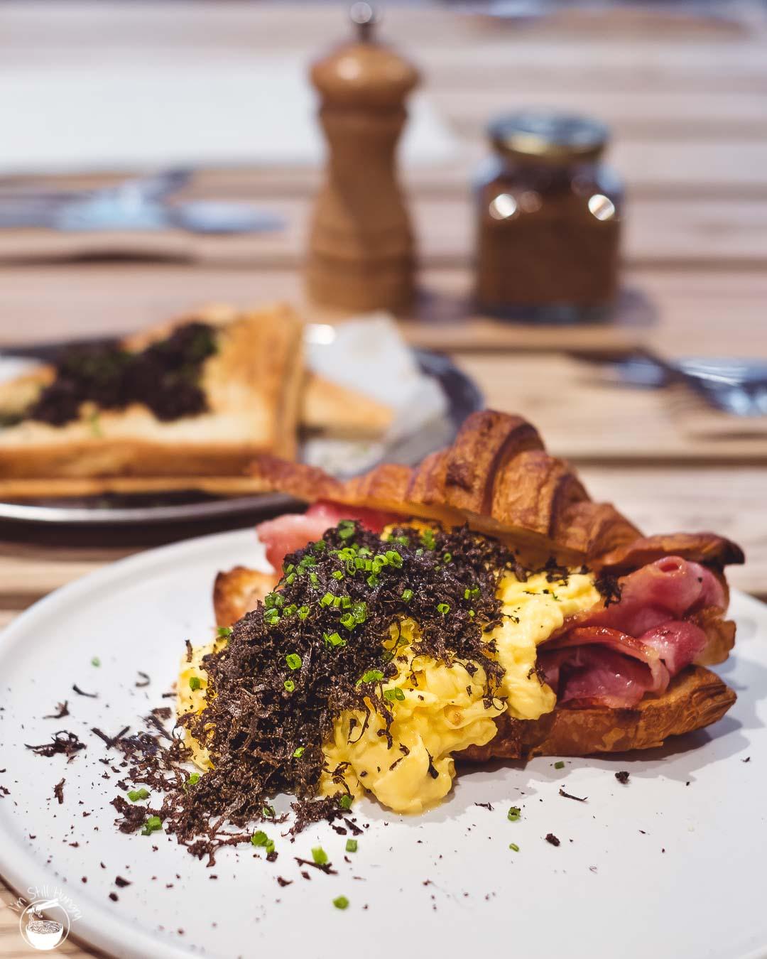 Devon Cafe Barangaroo Croissant royale: butter croissant, scrambled eggs, bacon, fresh WA truffle